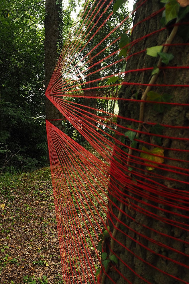 installatie kunstenlandschap 2019; ruimtelijk werk met tussen bomen gespannen rood draad
